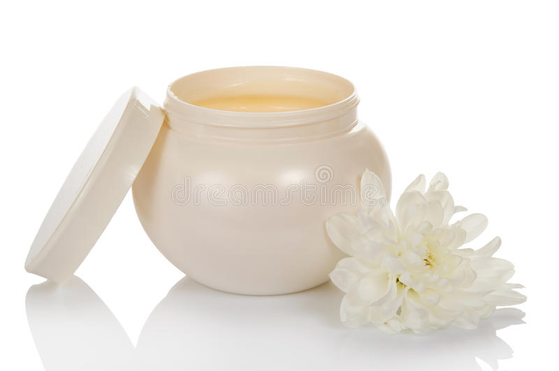 Open jar with a face cream and flower. Open jar with a face cream and a flower, isolated on white royalty free stock photography