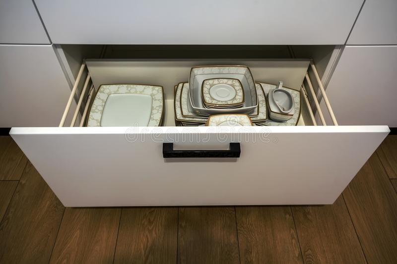 Open kitchen drawer with plates inside, a smart solution for kitchen storage and organizing. Open kitchen drawer with plates ine, a smart solution for kitchen stock photo