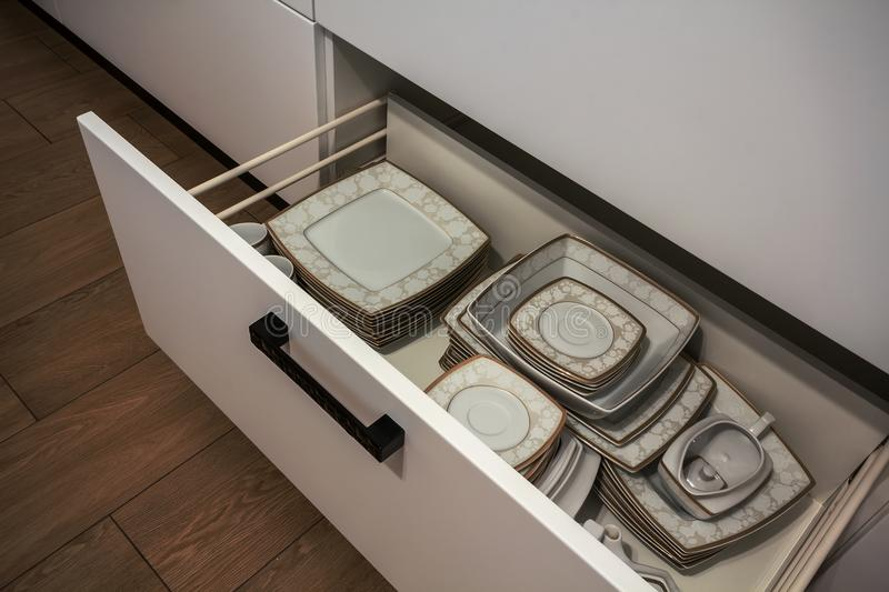 Open kitchen drawer with plates inside, a smart solution for kitchen storage and organizing.  royalty free stock images