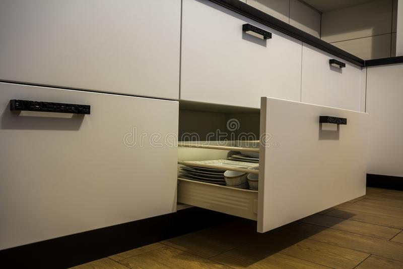 Open kitchen drawer with plates inside, a smart solution for kitchen storage and organizing.  stock photography