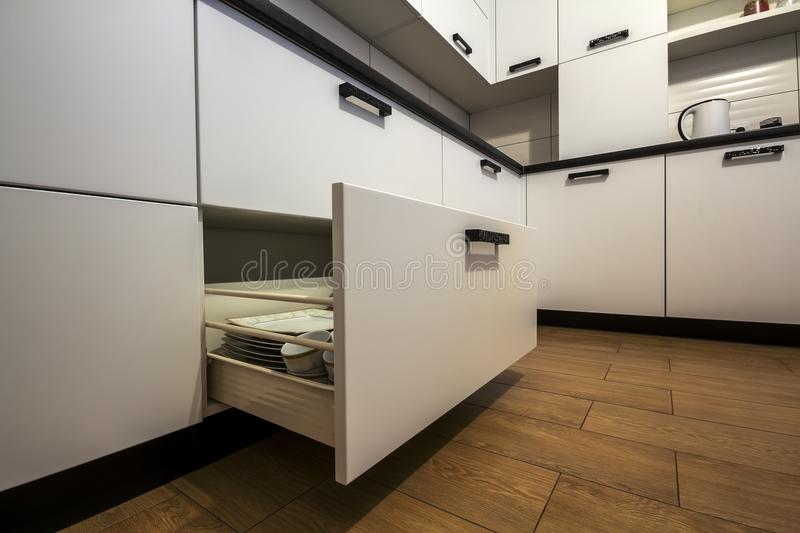 Open kitchen drawer with plates inside, a smart solution for kitchen storage and organizing.  stock image