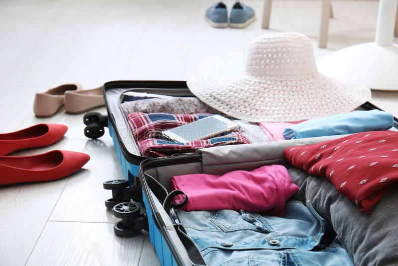 Open koffer met kleren en vrouwelijke schoenen op vloer stock afbeelding