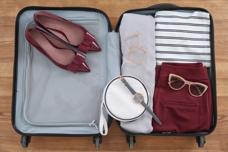 Open koffer met vrouwelijke kleding, schoenen royalty-vrije stock foto's