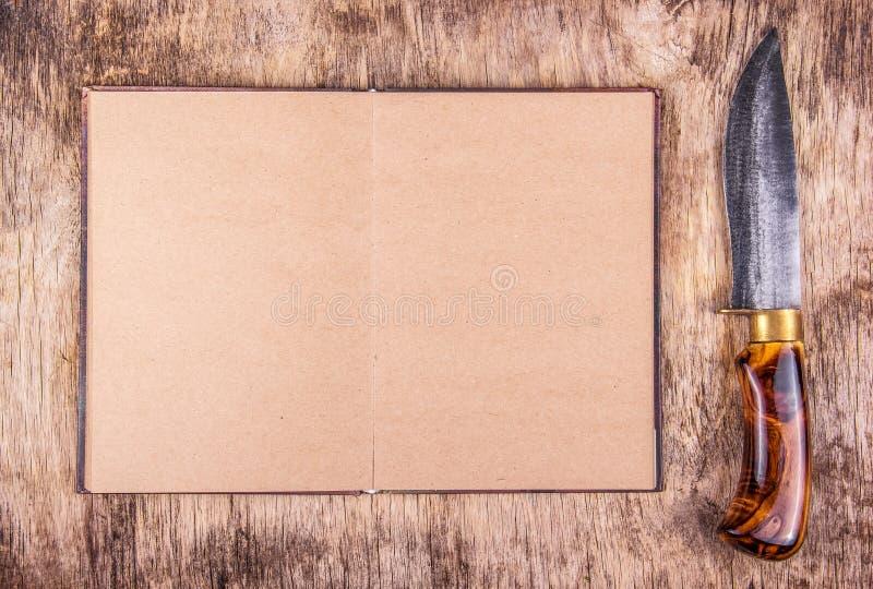 Open kookboek en keukenmes Leeg boek en mes stock afbeelding
