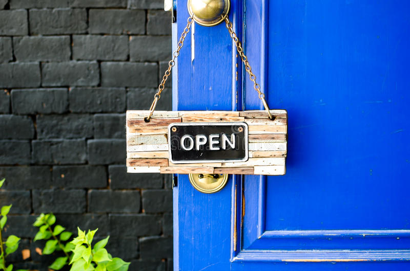 Open label hanging on blue door in garden.  royalty free stock image