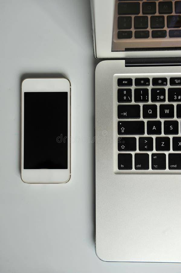 Open laptop en smartphone op witte lijst royalty-vrije stock afbeeldingen