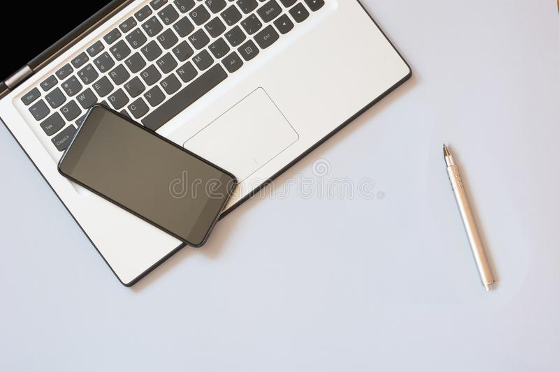 Open laptop and mobile on blue. Business concept. Top view. Copy space. Open laptop and mobile on blue background. Business concept. Top view. Copy space royalty free stock images