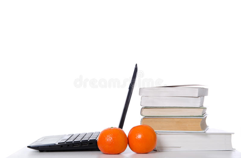 Open laptop, stack of books. And tangerines royalty free stock images