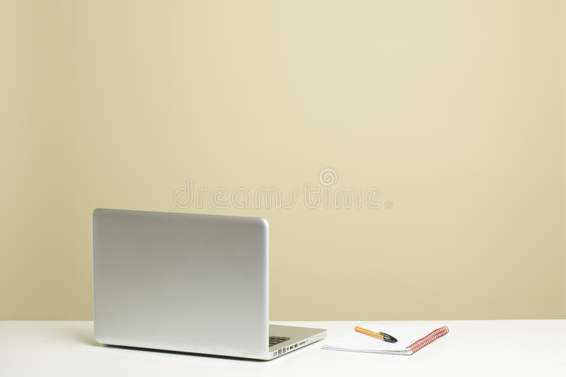Open laptop on white desk with note pad stock image