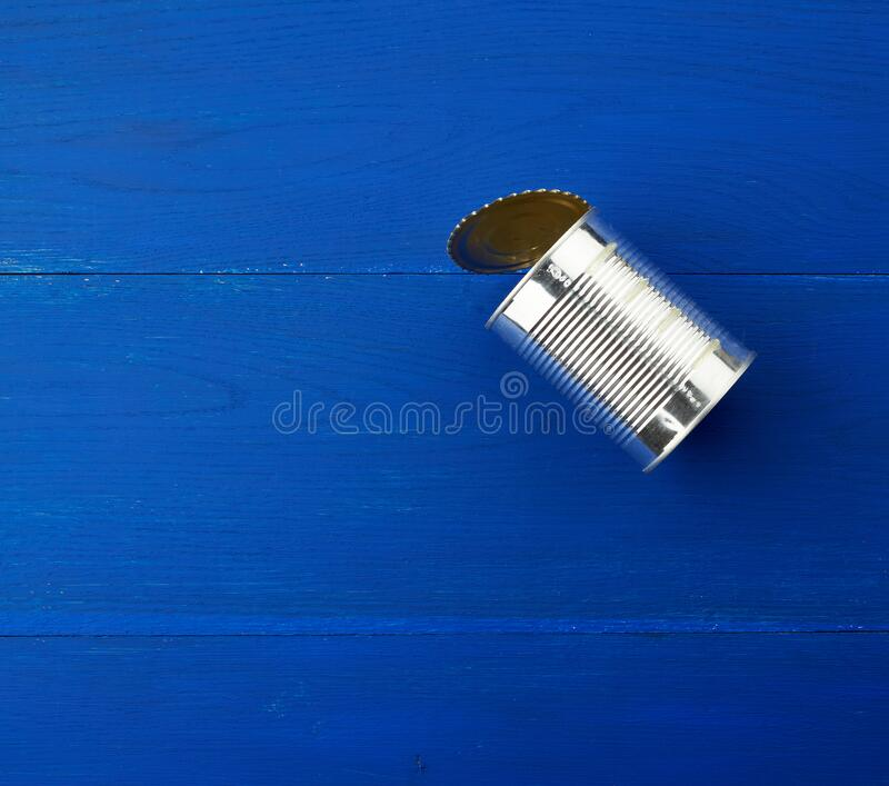 Open large metal tin can on a blue wooden background from parallel boards royalty free stock image
