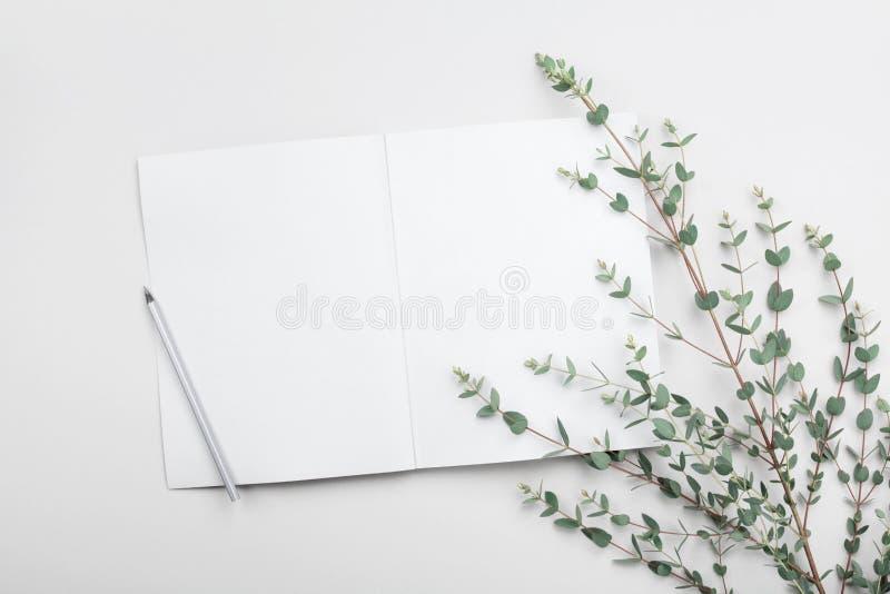 Open leeg notitieboekje en eucalyptusblad op grijze lijst van hierboven Minimalistic werkend bureau Vlak leg het stileren royalty-vrije stock afbeelding