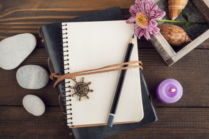 Open leeg notitieboekje, kiezelstenen, aangestoken kaars, bloem stock afbeeldingen