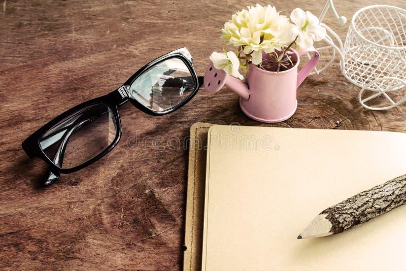 Open leeg notitieboekje met bloem en glazen op houten lijst stock fotografie