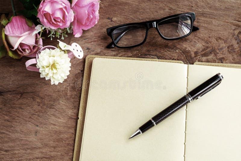 Open leeg notitieboekje met bloem en glazen op houten lijst stock afbeelding