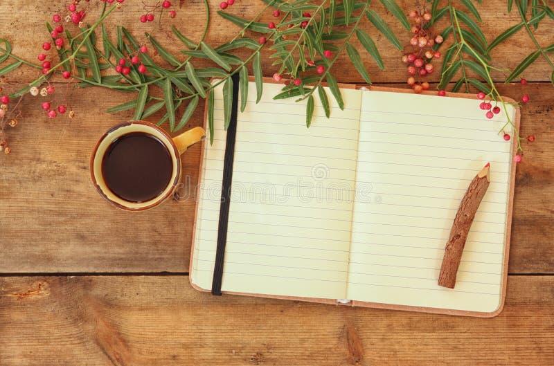 Open leeg uitstekend notitieboekje en houten potlood naast hete kop van coffe over houten lijst klaar voor model retro gefiltreer stock foto