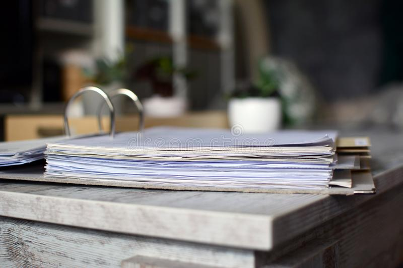 Lever arch file with many pages of documents lying on table with blurry background stock photography