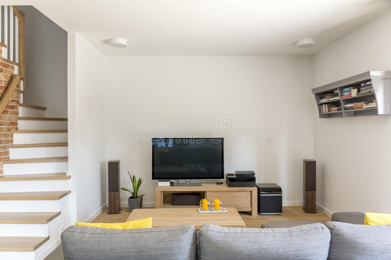 Open living room with tv. Sofa and staircase royalty free stock photo