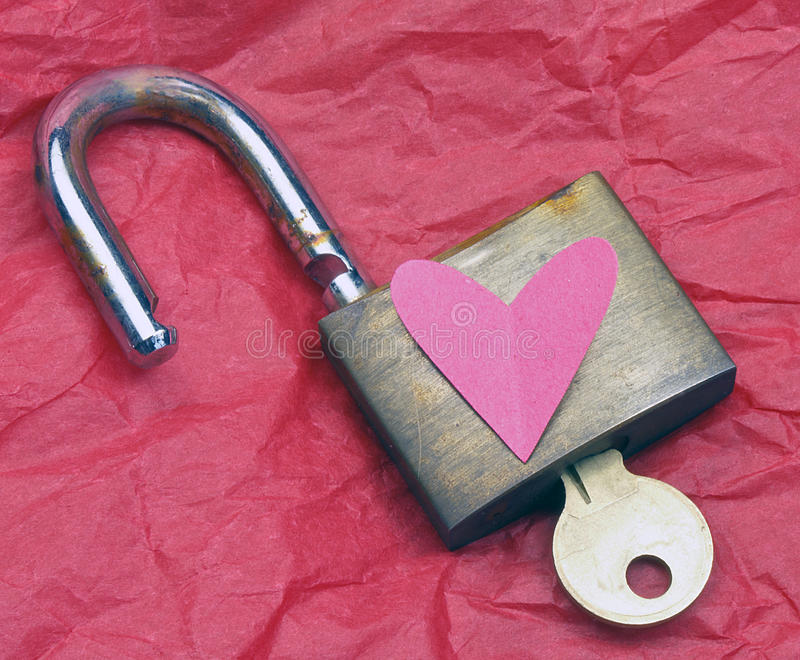 Open lock and key. On red tissue paper royalty free stock photo