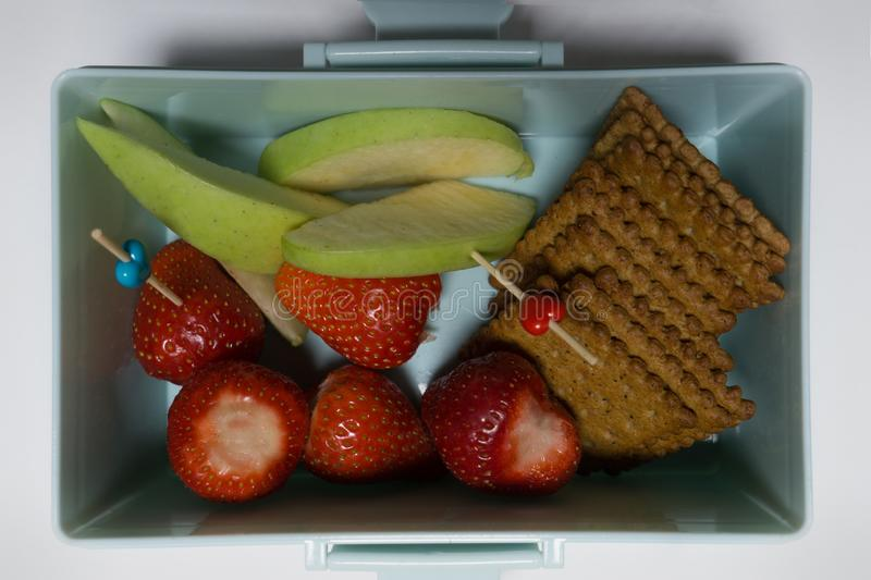 Open lunch box with banana berries and crackers royalty free stock images