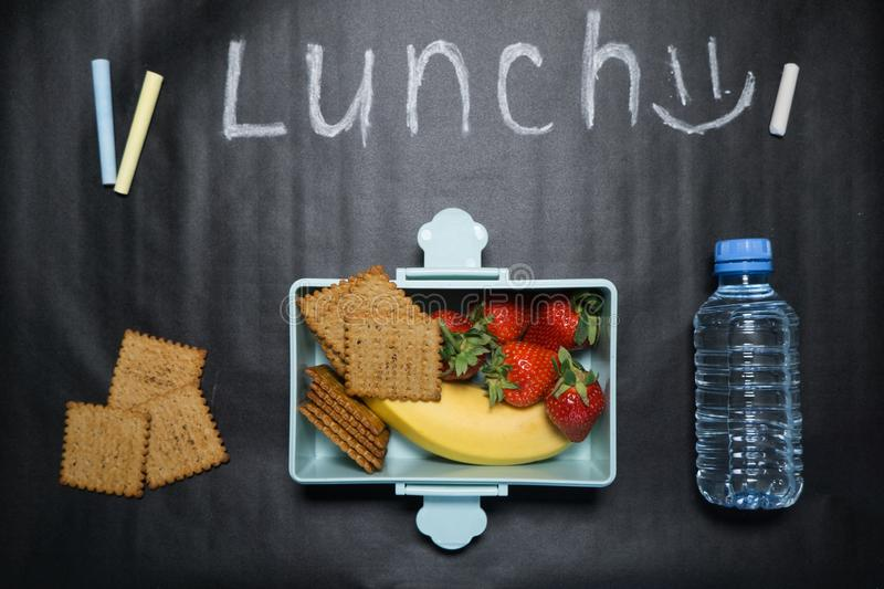Open lunch box with banana berries and crackers and a bottle of water on a black background with colorful crayons and lunch royalty free stock photos