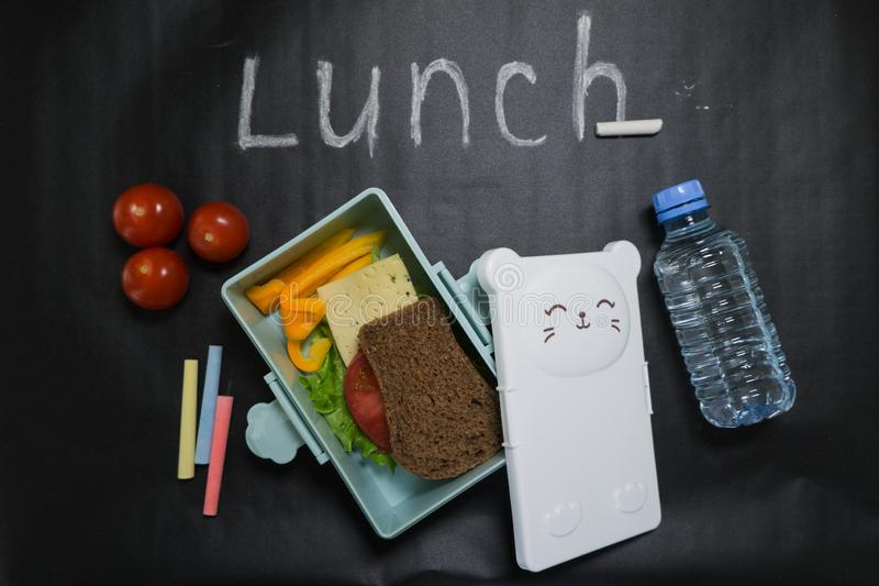 Open lunch box with a sandwich of whole grain bread, cheese, green salad, tomato, cucumber and a bottle of water on a stock photography