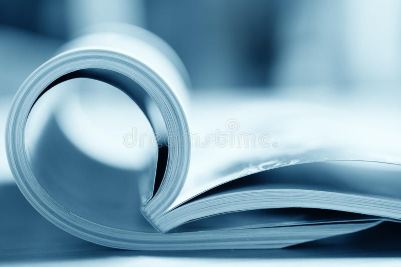 Open Magazine. With focus on front edge. Blue toned image stock photography