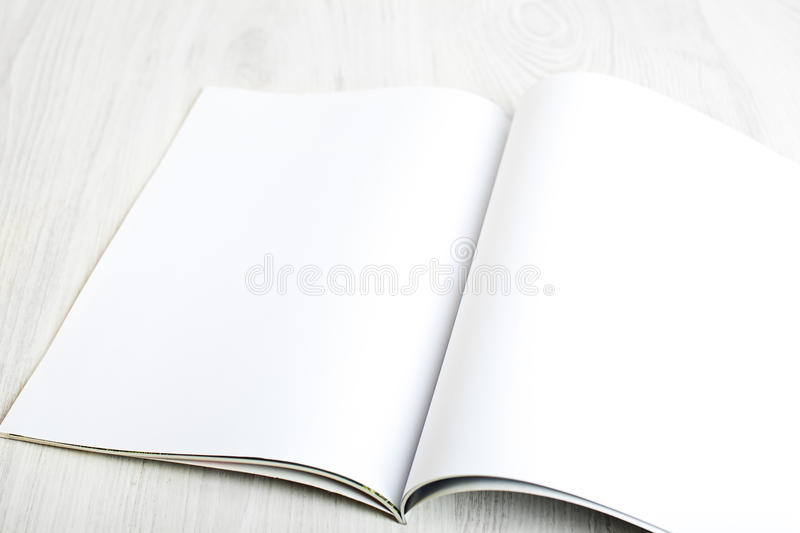 Open magazine with blank pages. On white table royalty free stock photo