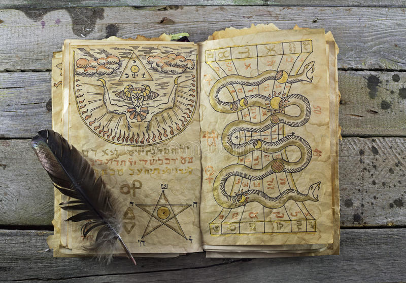 Open magic book 2. Halloween still life with open magic book and quill on the table stock image