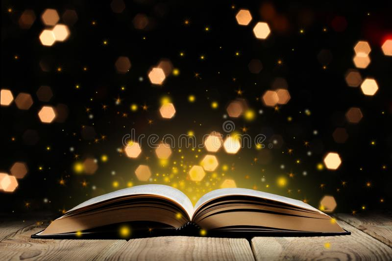 Open magic book on a wooden table with glitter and bokeh lights, and black background  with copy space for your text royalty free stock image