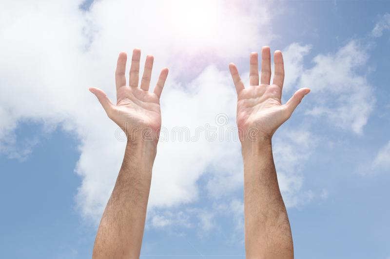 Open man`s hands rising up to the sky stock image
