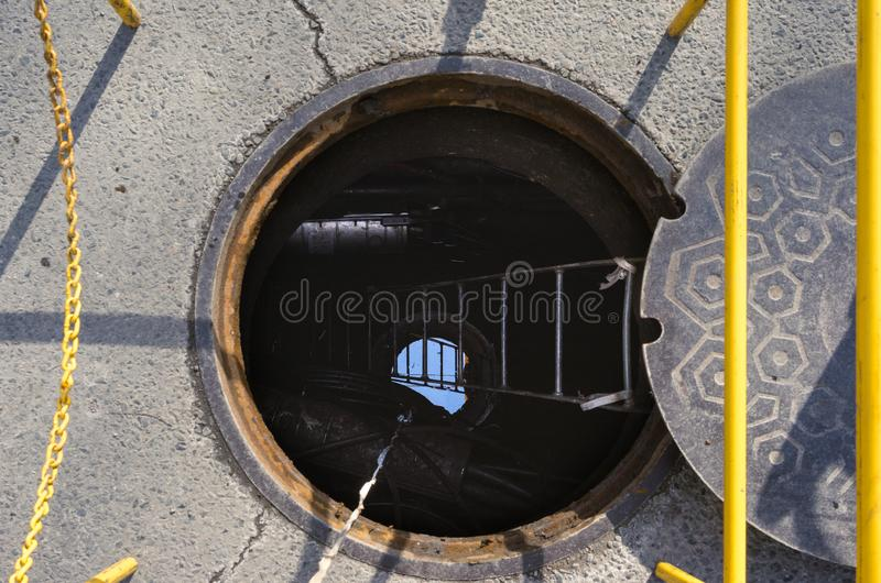 An open manhole on a city street. An open manhole for work access on an urban city street royalty free stock images