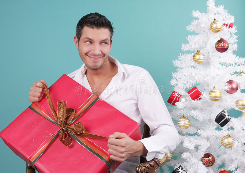 Open x-mas gift. Happy man opening christmas gift royalty free stock photo