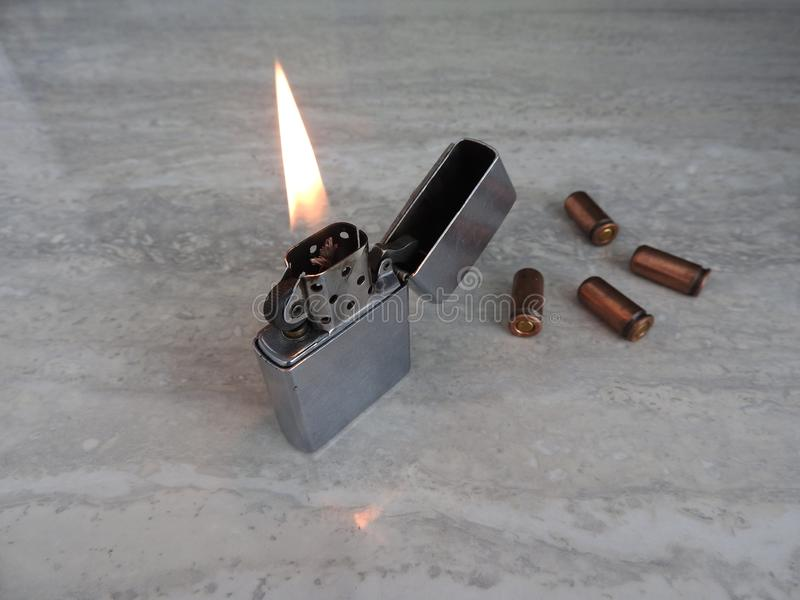 Open metal lighter with flame on black background. royalty free stock image