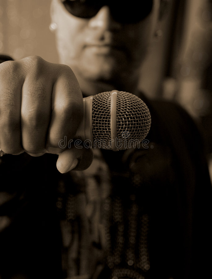 Open Mic. Rapper with a Microphone in his hand shallow depth of field sepia toned royalty free stock photo