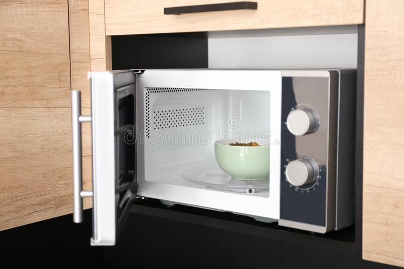 Open modern microwave oven with dish stock image