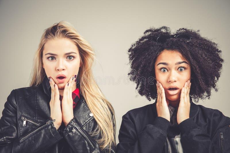 Open mond die van wauw Twee de verraste tienerhipstermeisjes hun gezichten toching royalty-vrije stock afbeelding