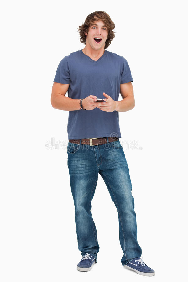 Download Open-mouthed Student Holding A Cellphone Stock Image - Image of jeans, leaning: 25335249