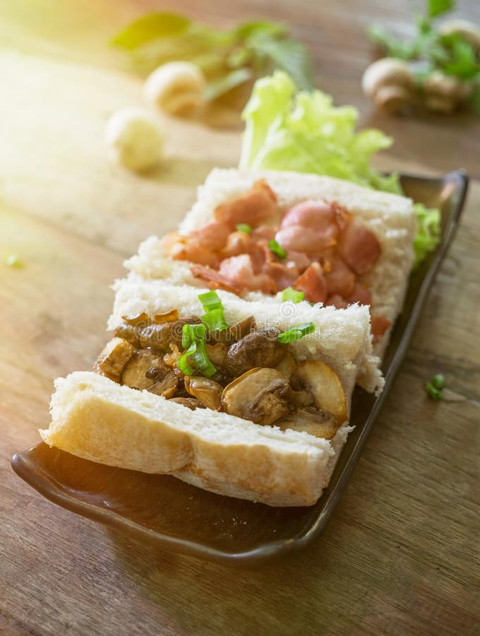 Open mushroom bacon sandwich with spring onion in plate on wooden table. Rustic food background royalty free stock photos
