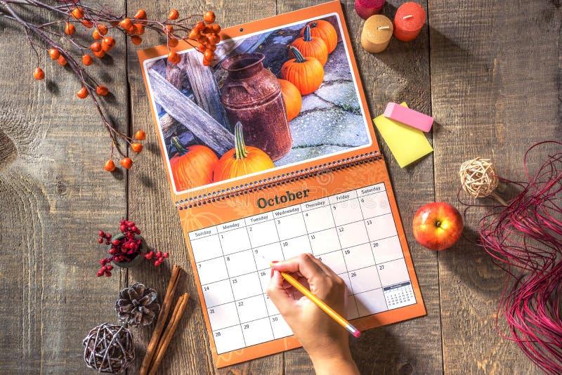 Open muurkalender met rustiek Oktober-beeld, vrouwelijke klaar hand stock afbeeldingen