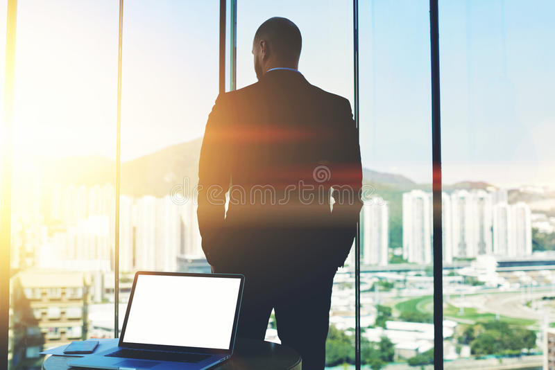 Open net-book with mock up copy space screen is lying on the table. Silhouette of man CEO is thinking about future of his company, while is watching in office stock image