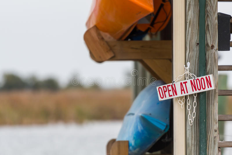 Open at Noon Sign with Two Kayaks. Hanging on ramp royalty free stock photo