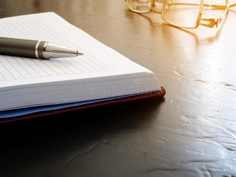 Open notastootkussen met pen en glazen Herinnering op het bureau royalty-vrije stock afbeelding