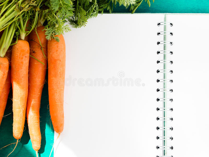 Open note book with blank pages and carrots. Open paper note book with blank pages on dark green table with carrots royalty free stock images