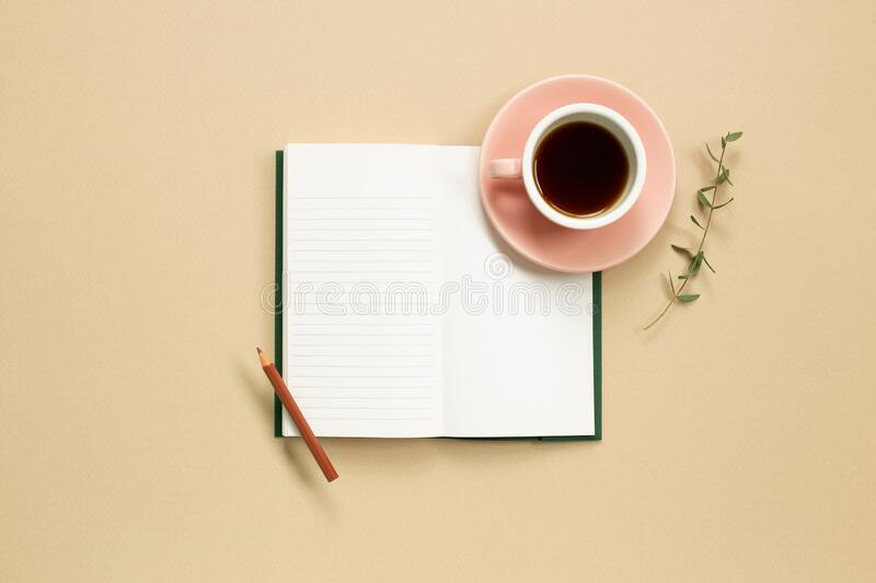 Open note book with cup of coffee on beige background. Flat lay, top view, copy space royalty free stock photography
