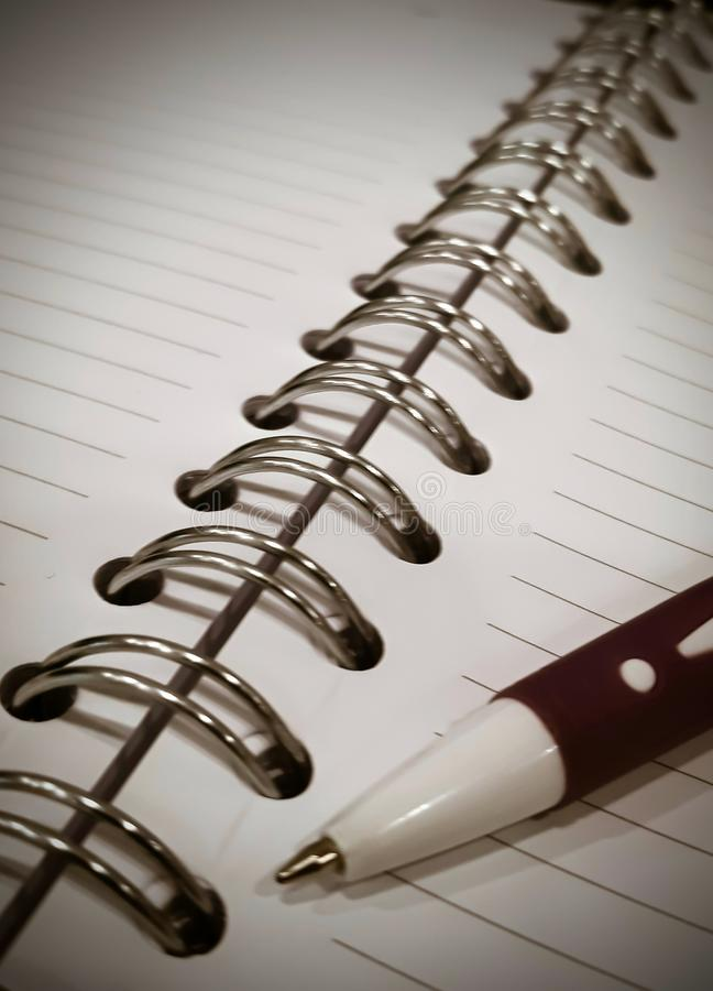 Open note book and metal spiral binding with pen view royalty free stock images