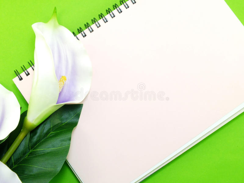 Open notebook and beautiful calla artificial violet flowers bouquet. Open notebook and beautiful calla artificial violet flowers stock photo