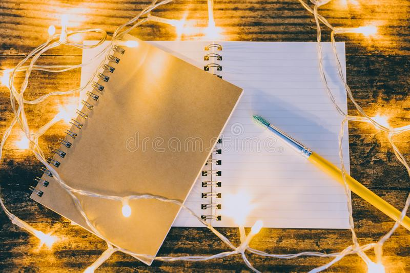 Open notebook with blank pages with copyspace and brush surrounded by fairy lights. Concept of creativity and imagination royalty free stock image