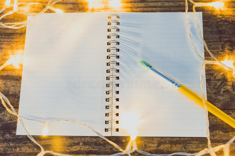 Open notebook with blank pages with copyspace and brush surrounded by fairy lights. Concept of creativity and imagination stock photography
