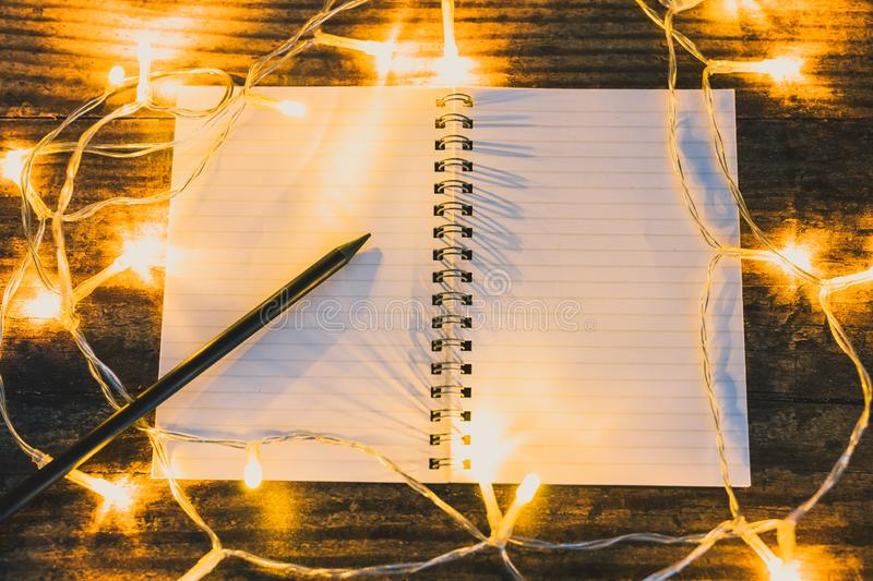 Open notebook with blank pages with copyspace and pencil surrounded by fairy lights. Concept of creativity and imagination royalty free stock images