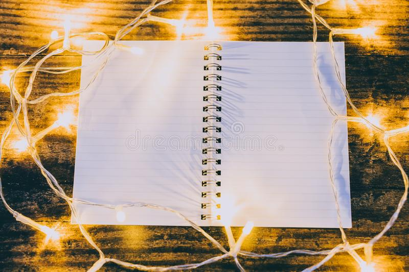 Open notebook with blank pages with copyspace surrounded by fairy lights. Concept of creativity and imagination stock photos